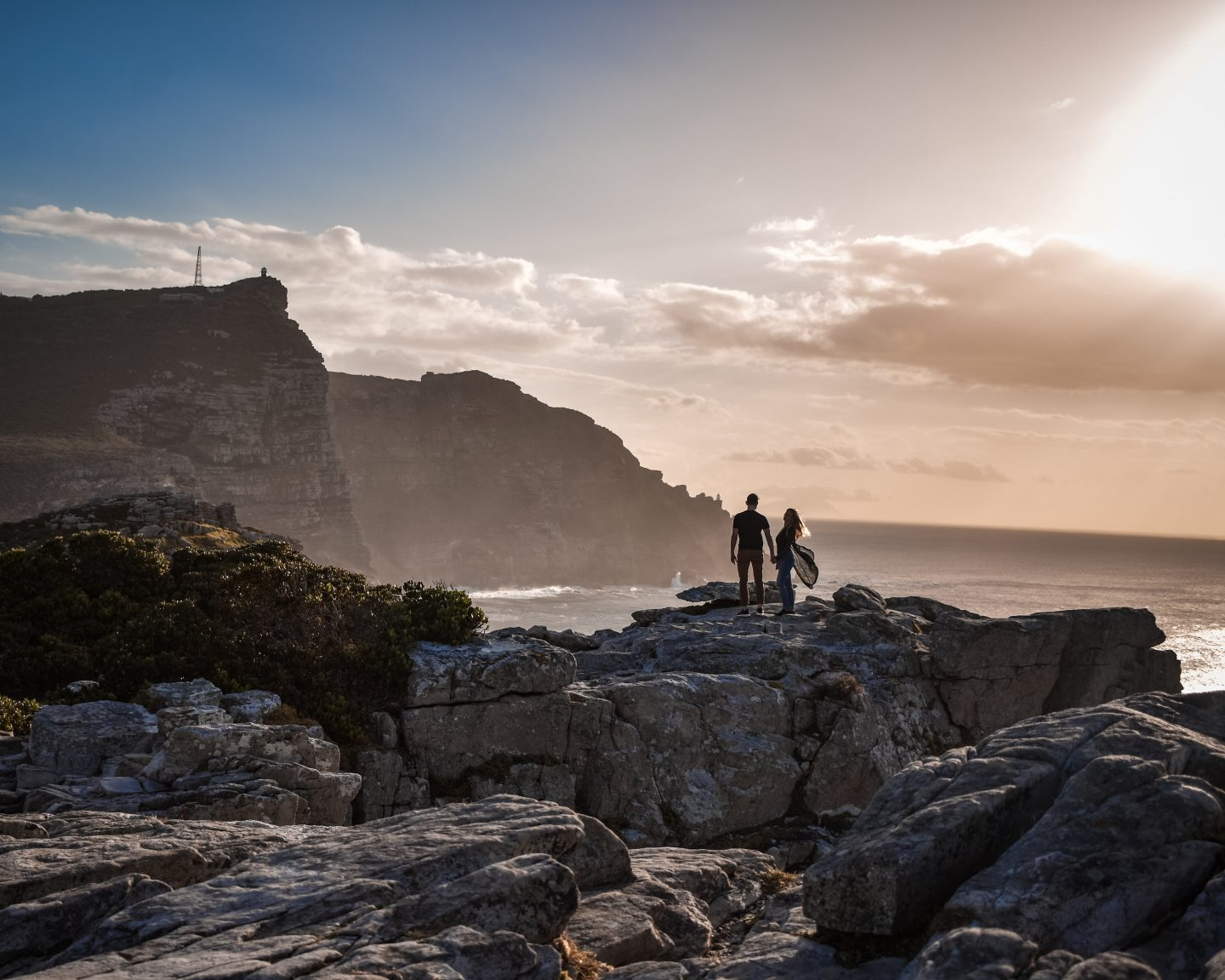 at sunrise a couple standing on a rock with ocean view