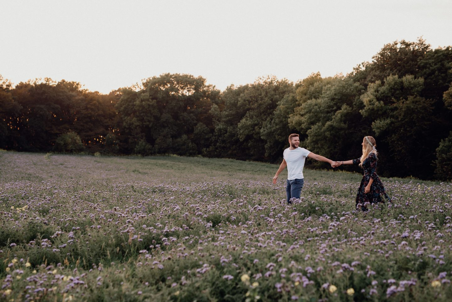couple standing in a field of purple flowers at sunset holding hands