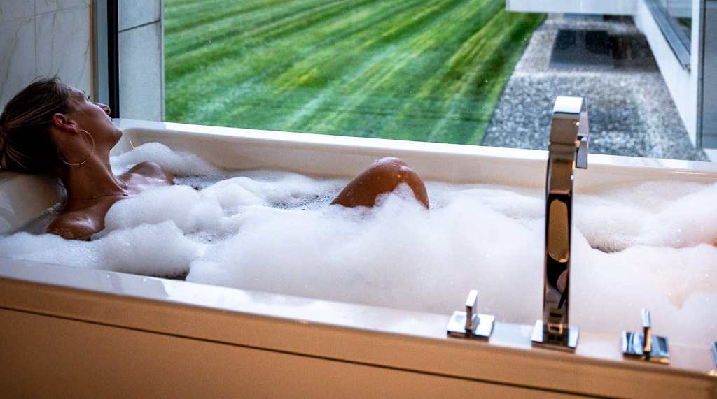 Person in the bathtub taking a full bath with a view to the garden. Showing the opposite of saving the climate.