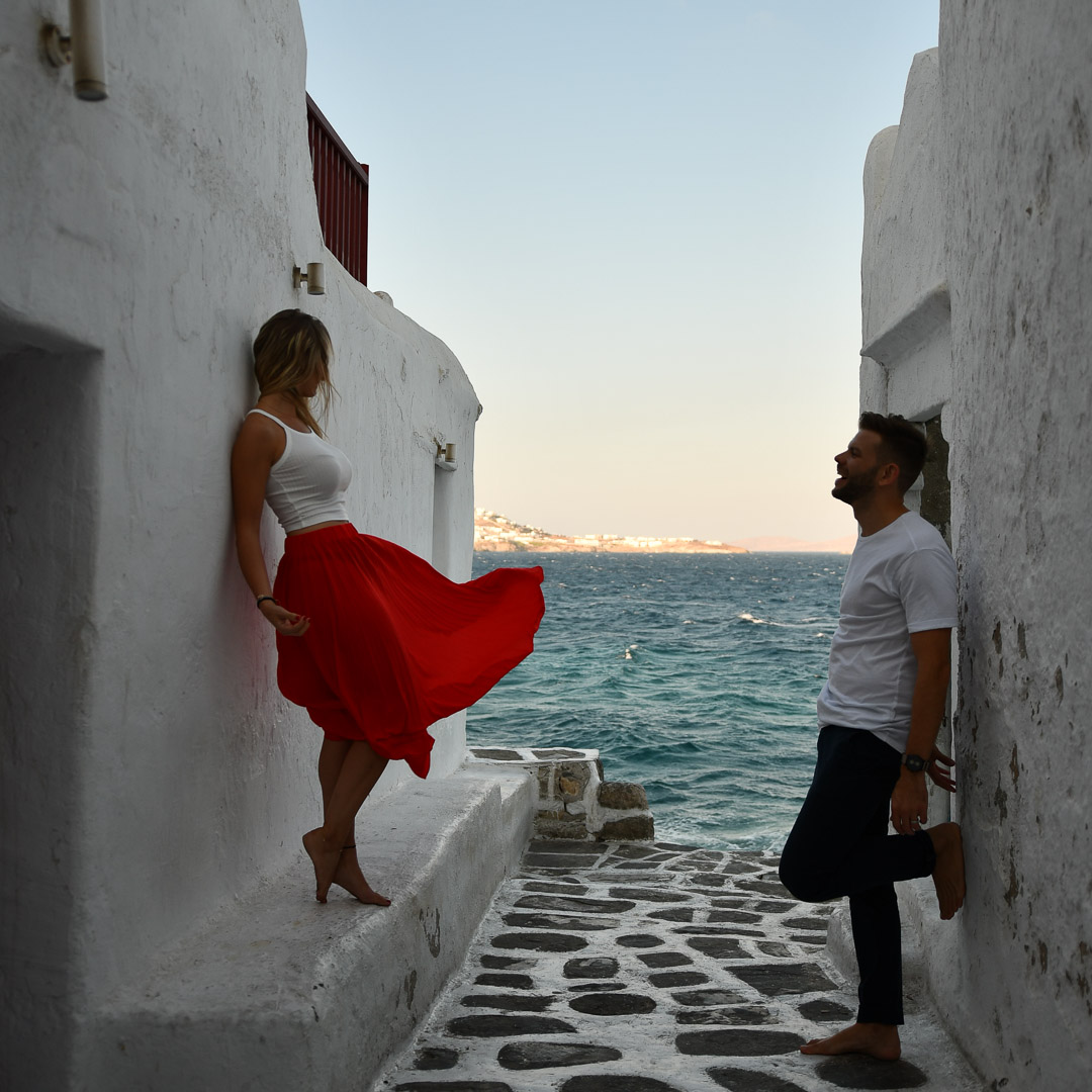 couple leaning in Mykonos on a white wall