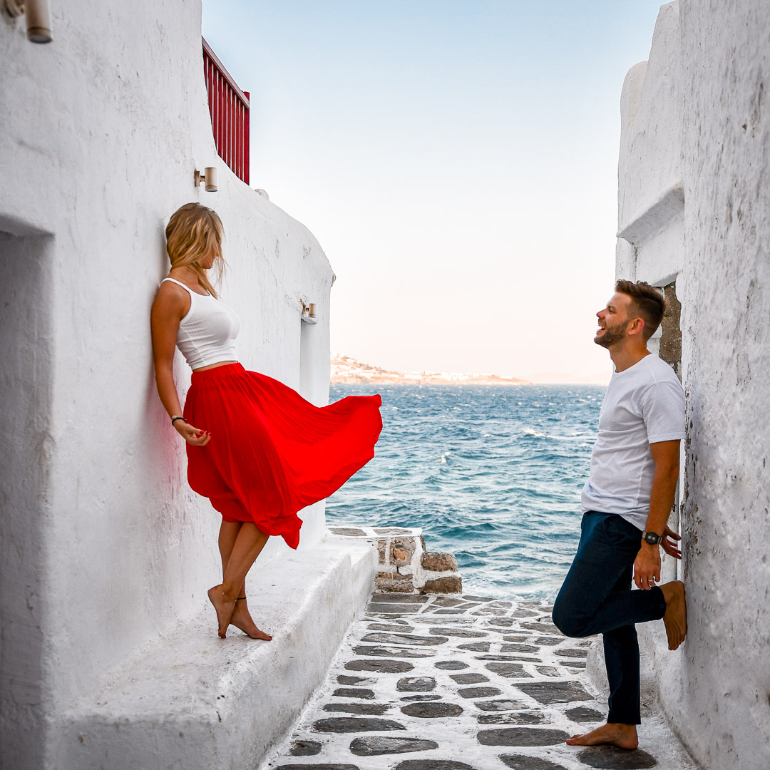 couple leaning in Mykonos on a white wall with ocean view