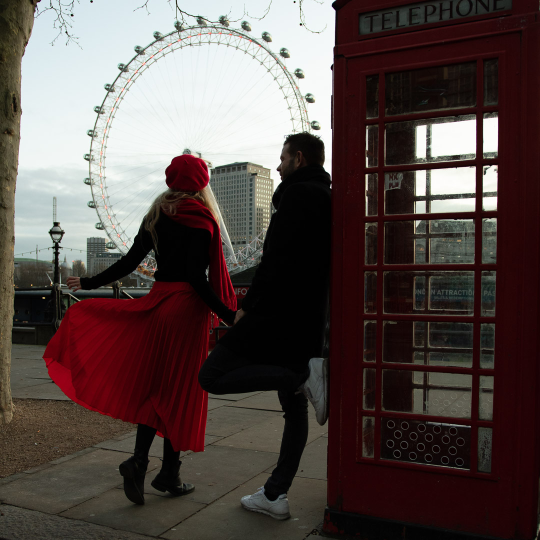 couple in London leaning on a telephone cabin