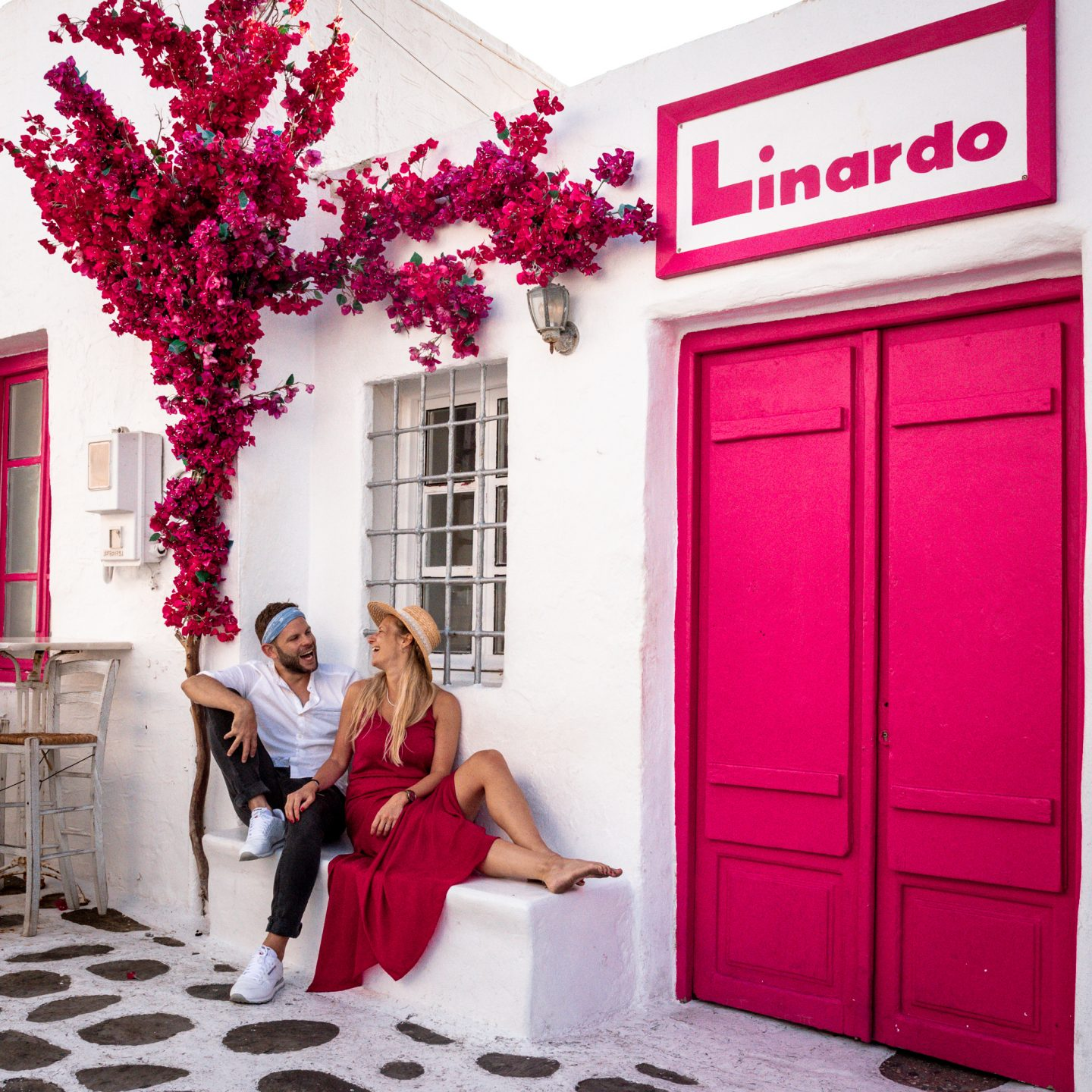 preset in usage: a colorful pink door in Greece and a couple sitting and laughing