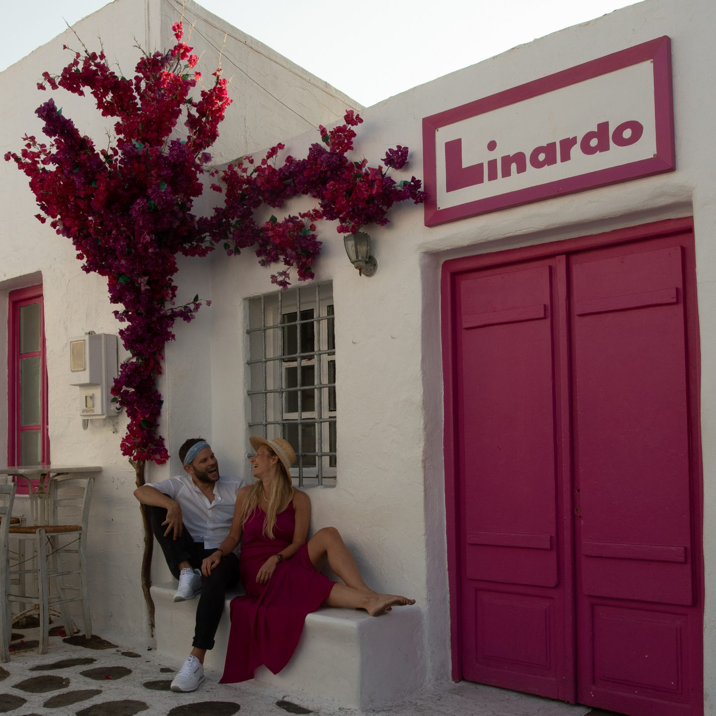 no preset in usage: a pink door in Greece and a couple sitting and laughing