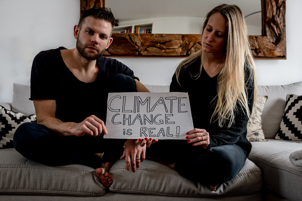 """Couple sitting on a couch holding a sign: """"Climate Change is real"""""""