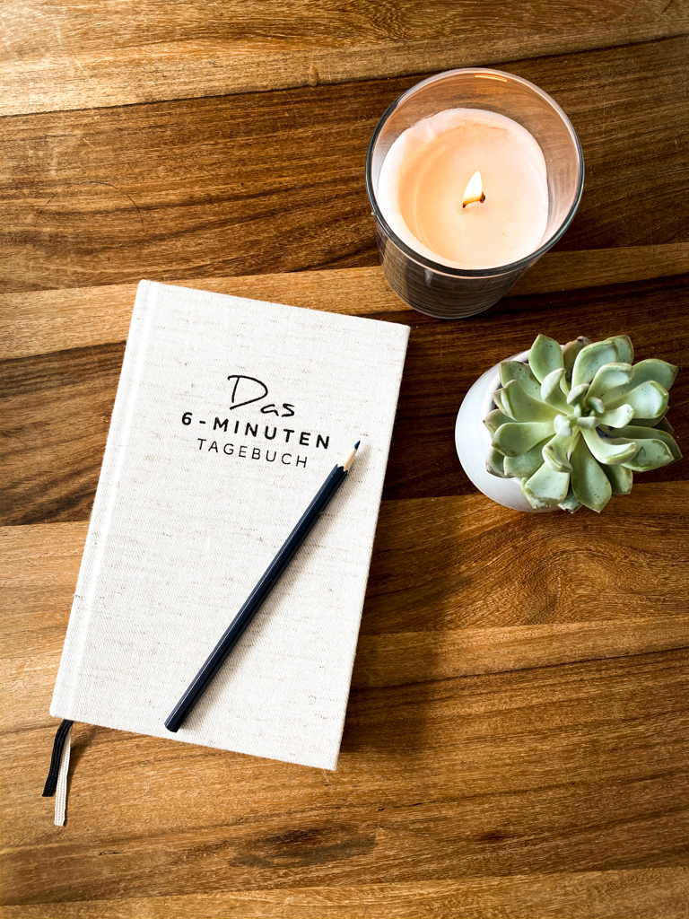 Diary with a pencil, a burning candle and a small plant beside it. One of our 8 habits we have evolved during corona isolation.