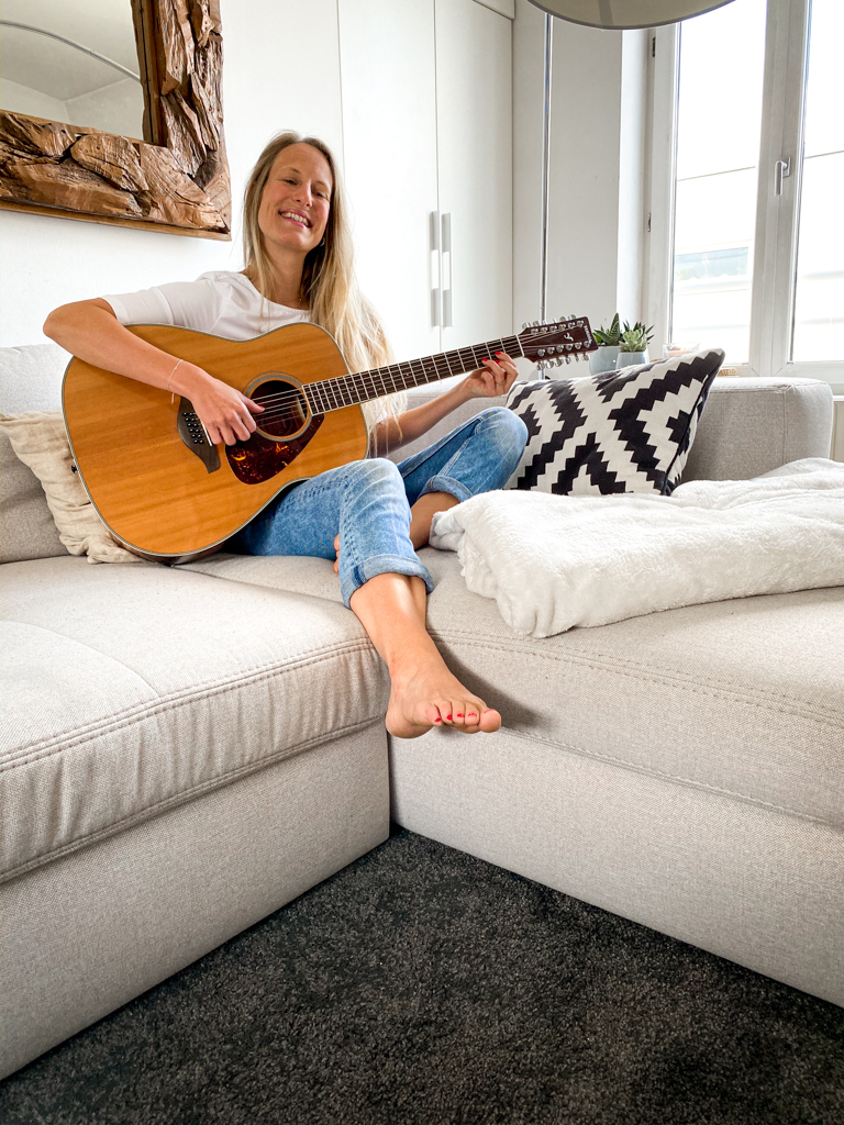 Woman sitting on the sofa playing guitar.