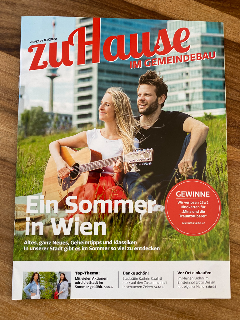 Picture of a Magazin, on the cover you can see a couple sitting in the grass infant of the skyline in Summer in Vienna