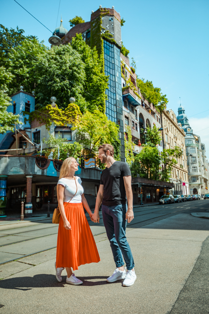 Couple looking at each other, standing on the street. In the back you can see the Hunderwasserhaus of Vienna in the summer