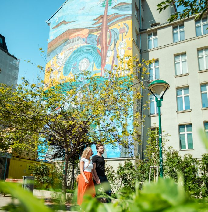 Couple walking along a tall house with a colorful graffiti on it. You can see green leaves in front