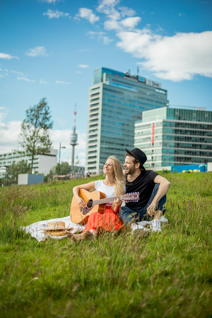 Couple sitting in the grass on a white blanket, the woman is playing the guitar, the man is laughing, you can see the Viennese skyline in the background