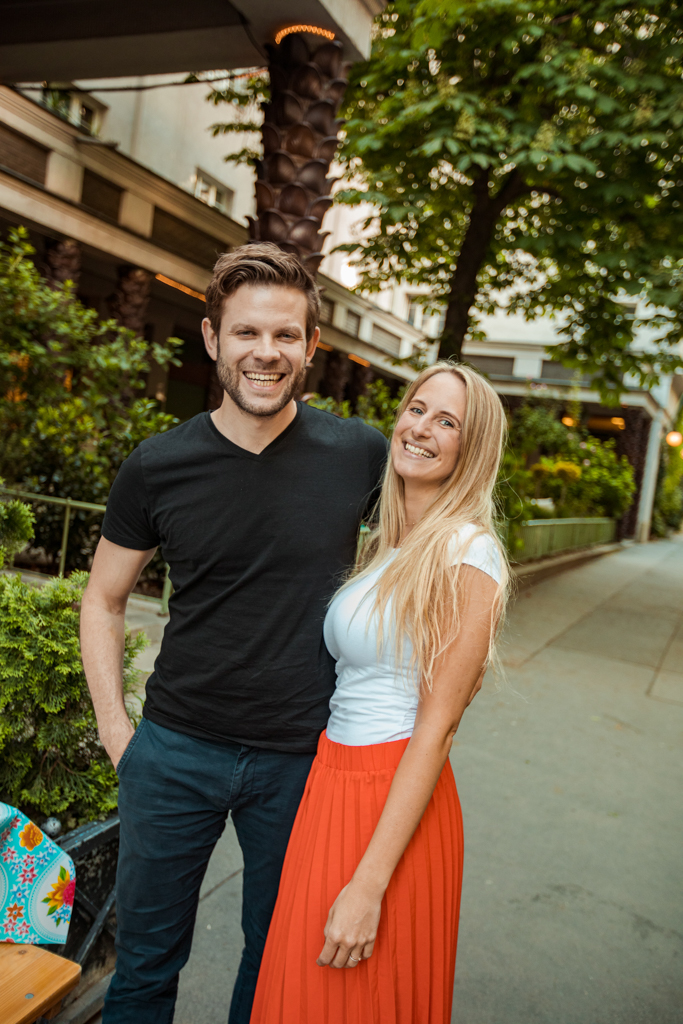 Couple standing outside before a tree laughing and looking into the camera