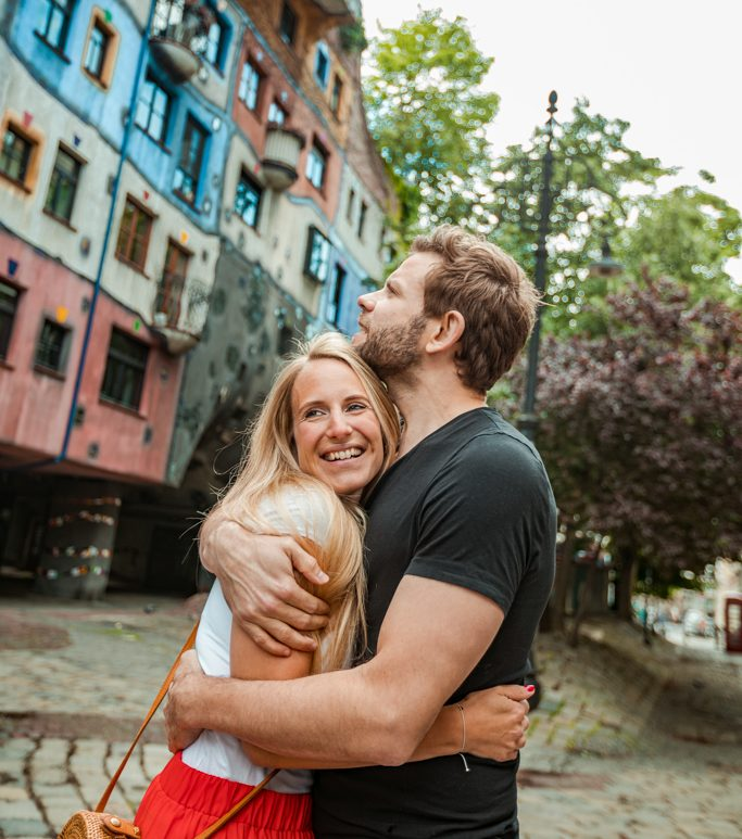 Coupe huggung, the girl is smiling and the guy is looking up. In the background you can see the Hundertwasserhaus of Vienna