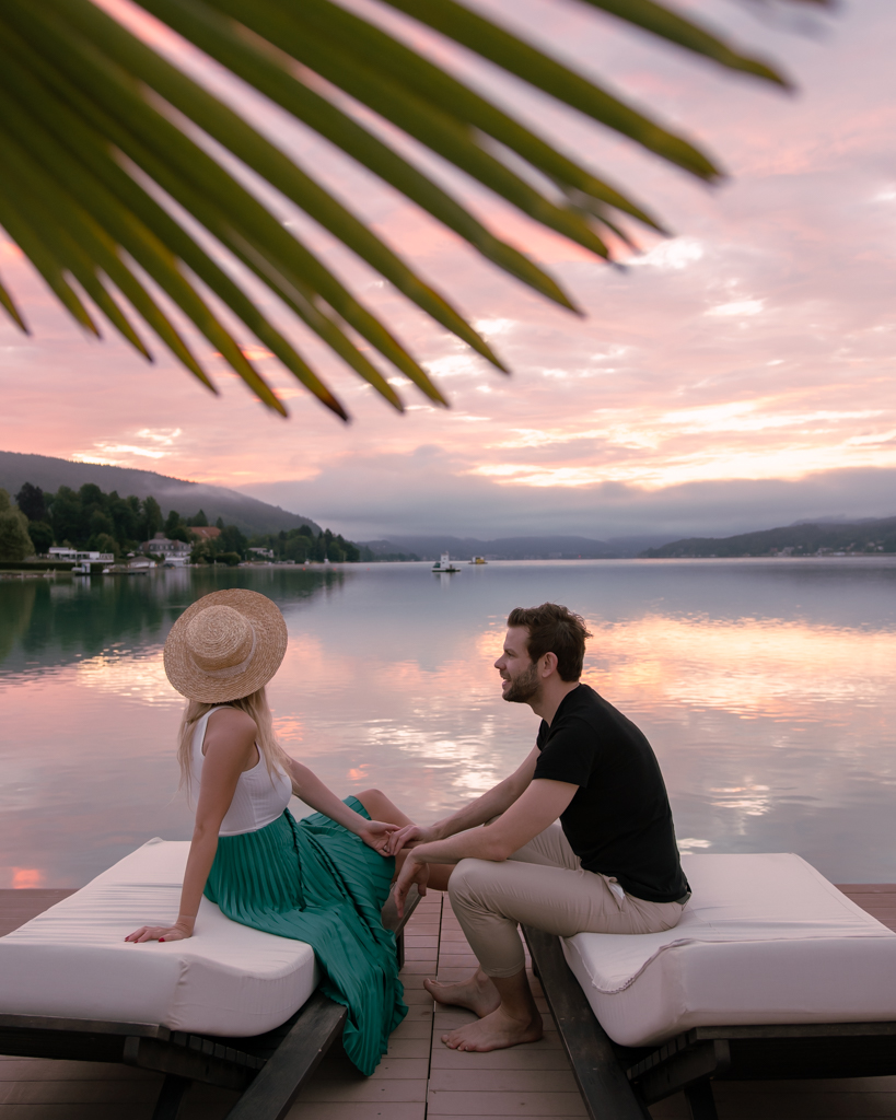 couple sitting at the side of Lake Wörthersee looking at the sunrise