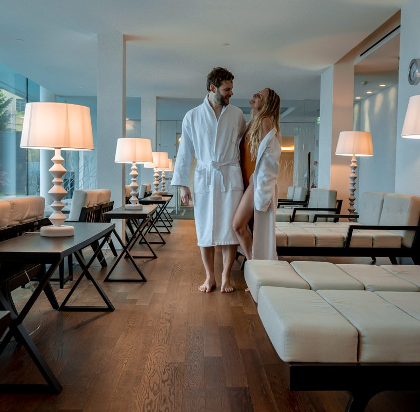 couple in bathrobes standing in the spa of the hotel