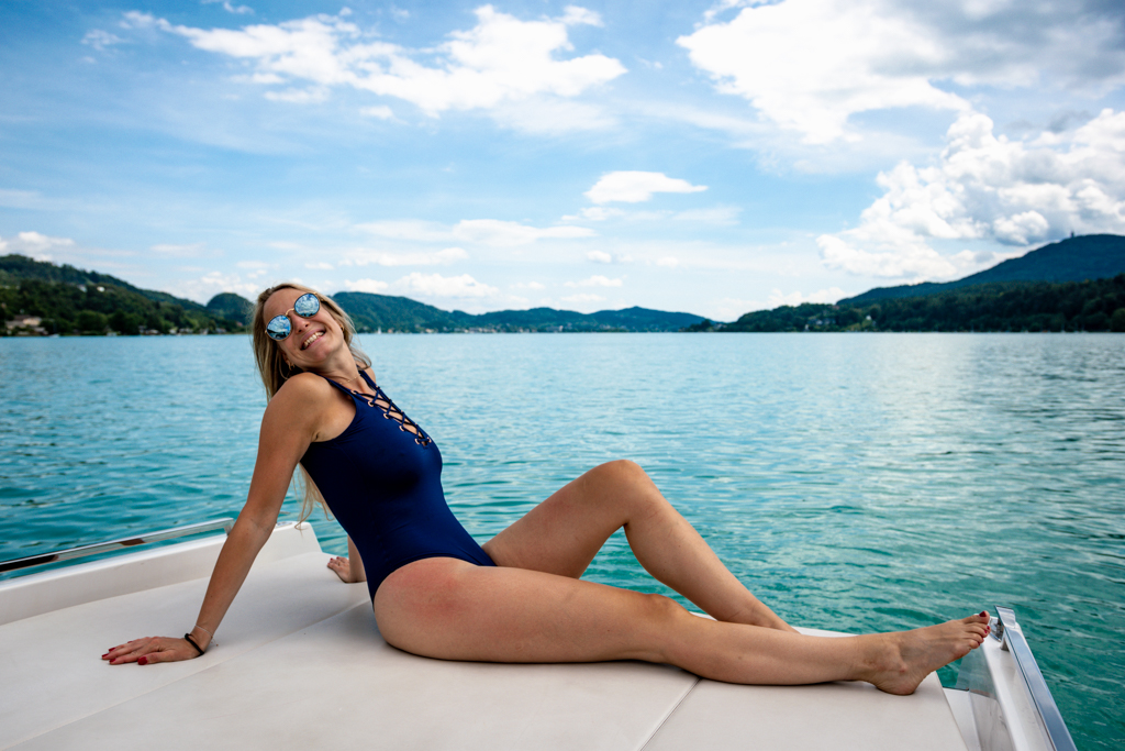 happy smiling girl sitting in a boat on a swimsuit at Lake Wörthersee
