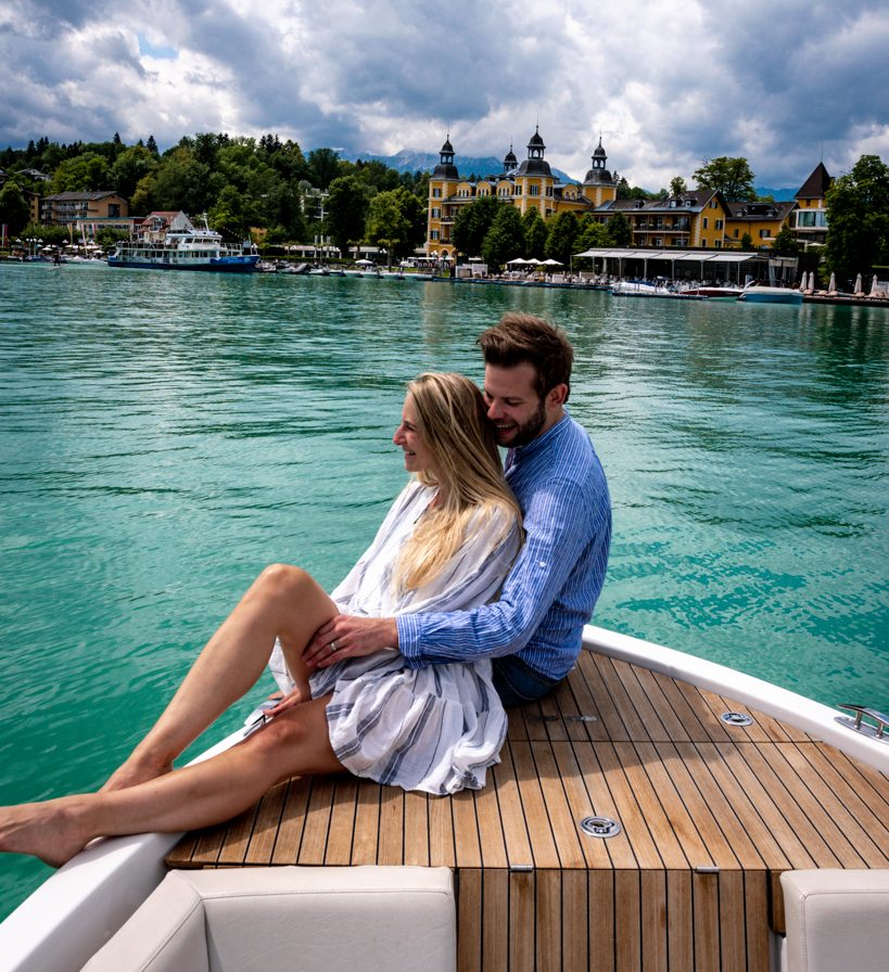 couple sitting on the edge of a boat in the back you can see the Schlosshotel velden