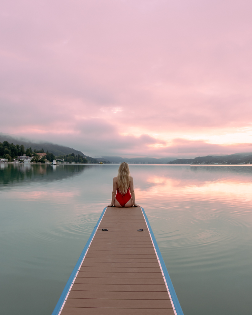 girl sitting on a dock at Lake Wörthersee at sunrise