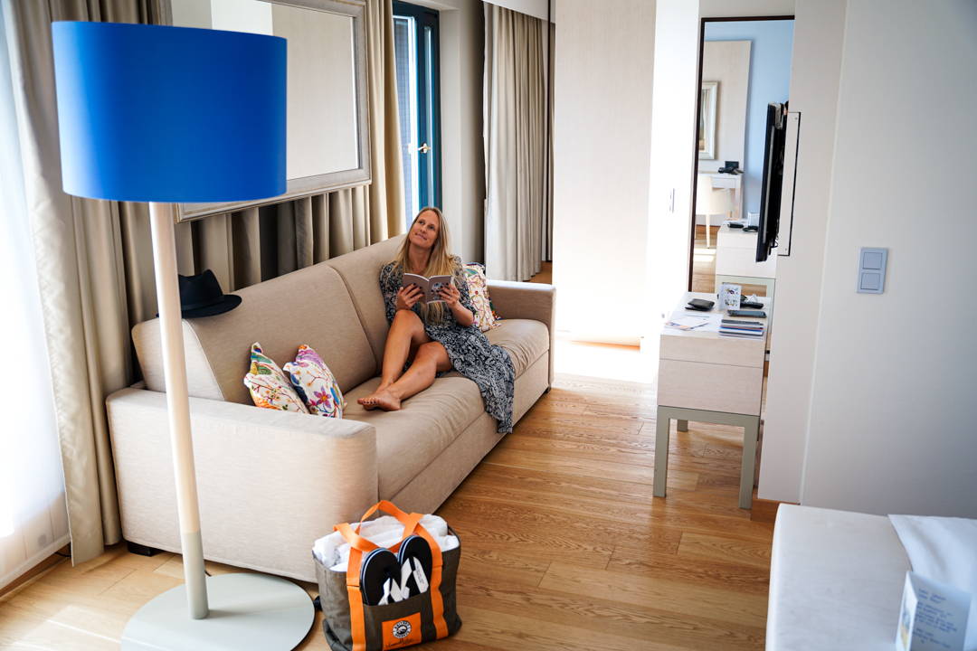 Woman sitting on a sofa in the hotel room of Reiters Supreme Hotel reading a brochure