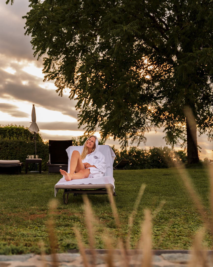 Woman sitting on a sun lounger in front of e tree