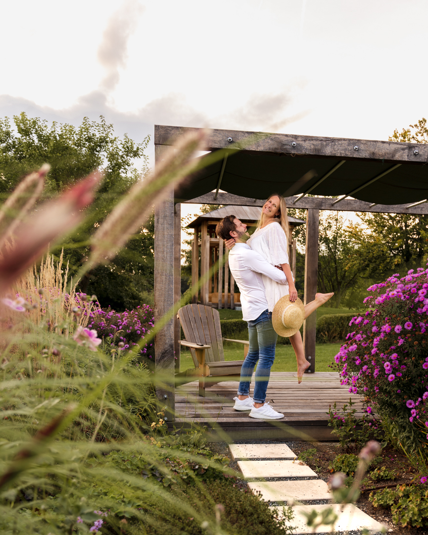 man carrying a woman in a white dress in front of a wooden pergola with wooden chairs framed by purple flowers