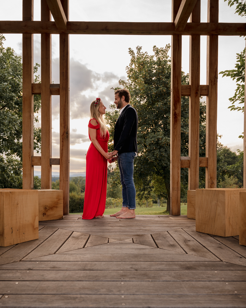 couple standing in a wooden pergola looking at each other, the woman wearing a red dress
