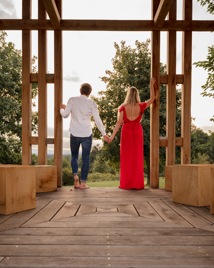 back view of a couple standing in a wooden pergola looking away, the woman wearing a red dress