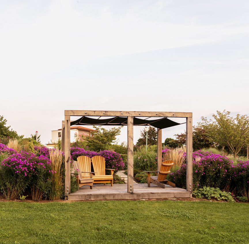 wooden pergola with wooden chairs framed by purple flowers
