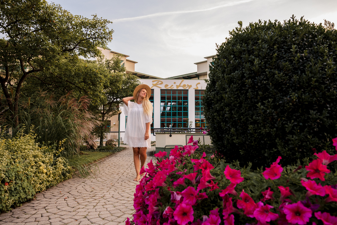 Woman in white dress in front of Reiters Reserve Entrance, pink flowers in front