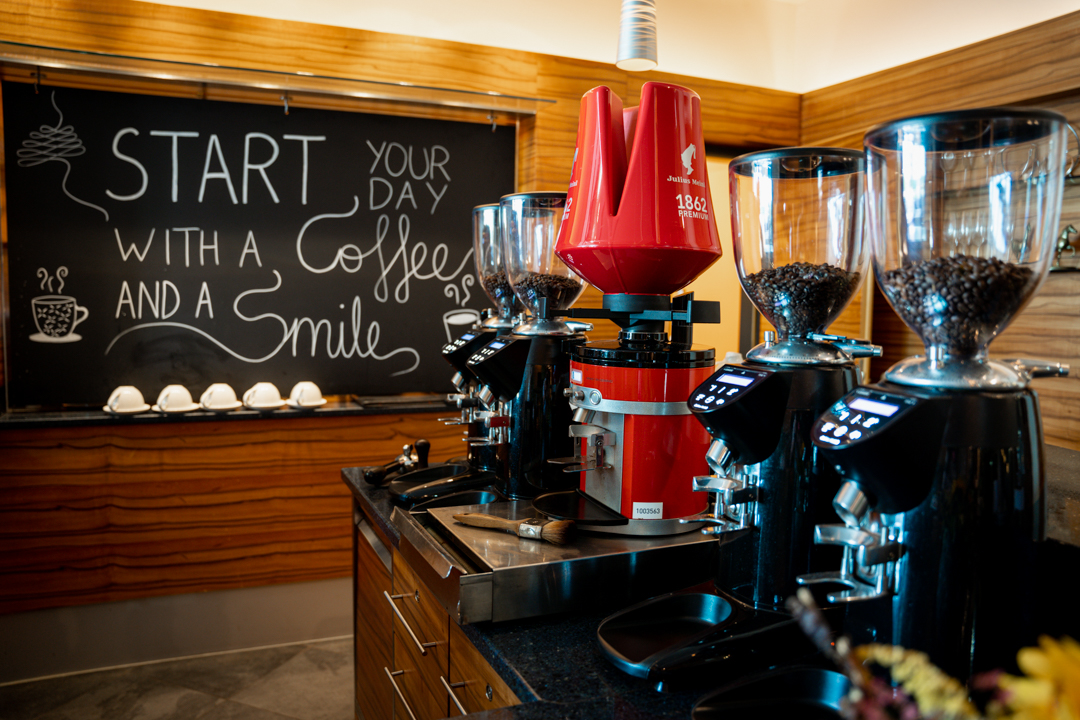 coffee maker and different coffee beans and a sign saying start your day with a coffee and a smile