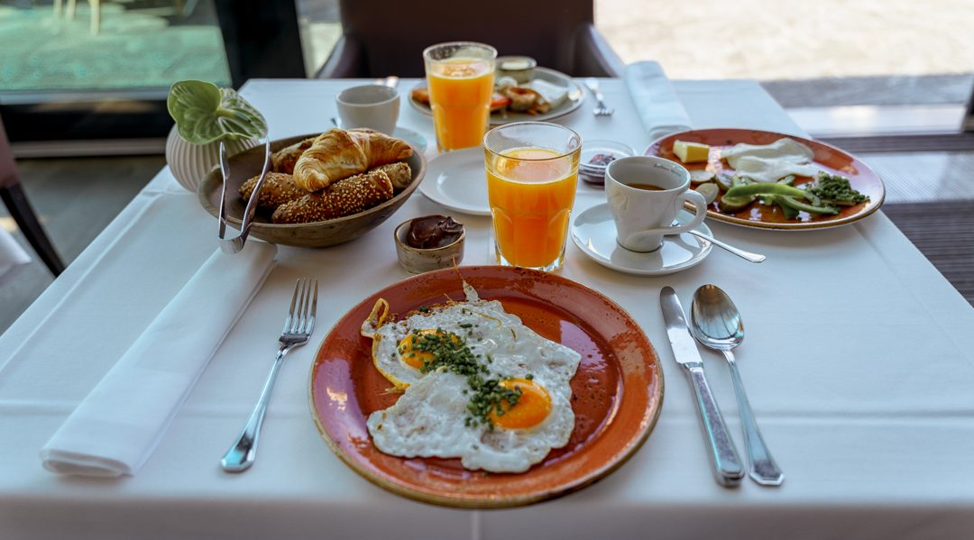 portrait of a breakfast table with eggs, juice and bread