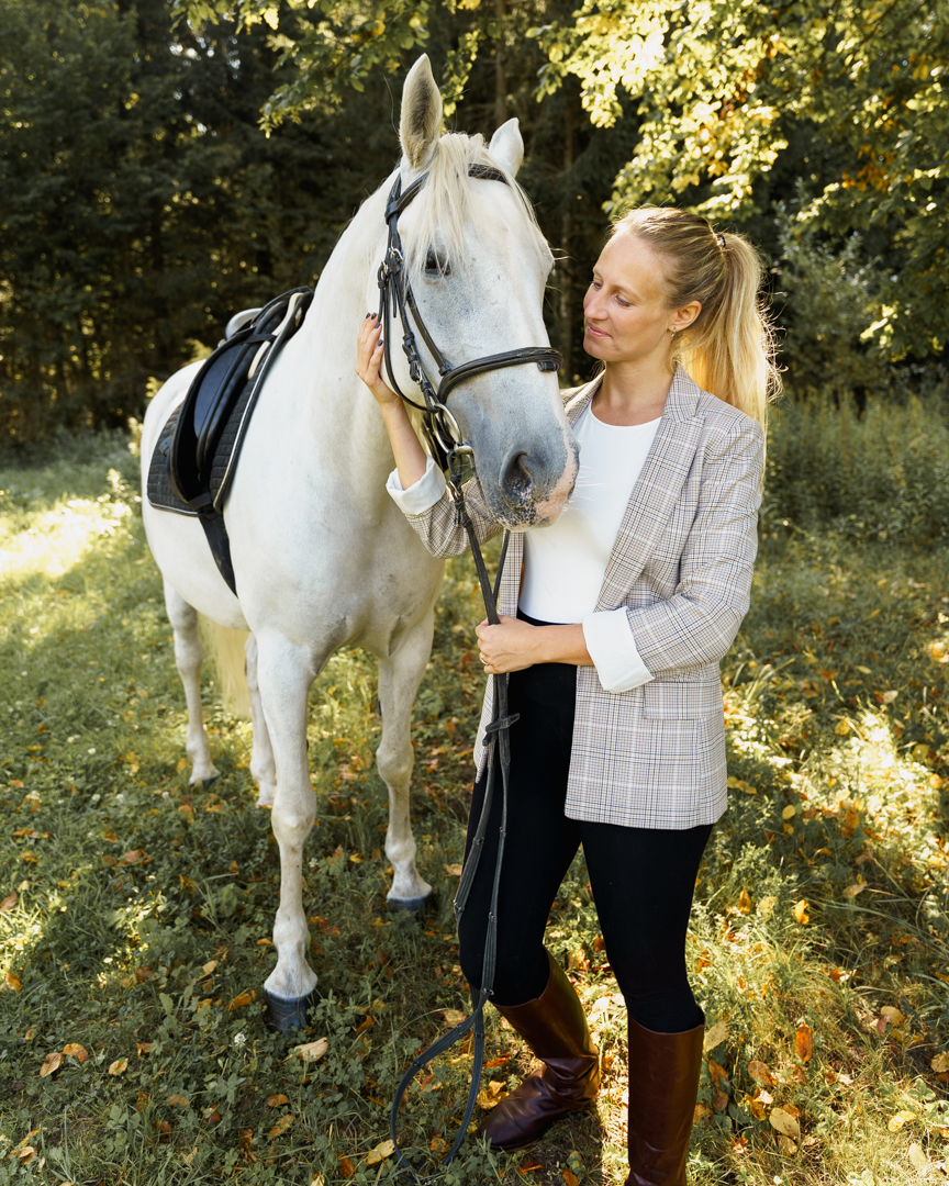 woman in riding outfit holding a white Lipizzaner horse