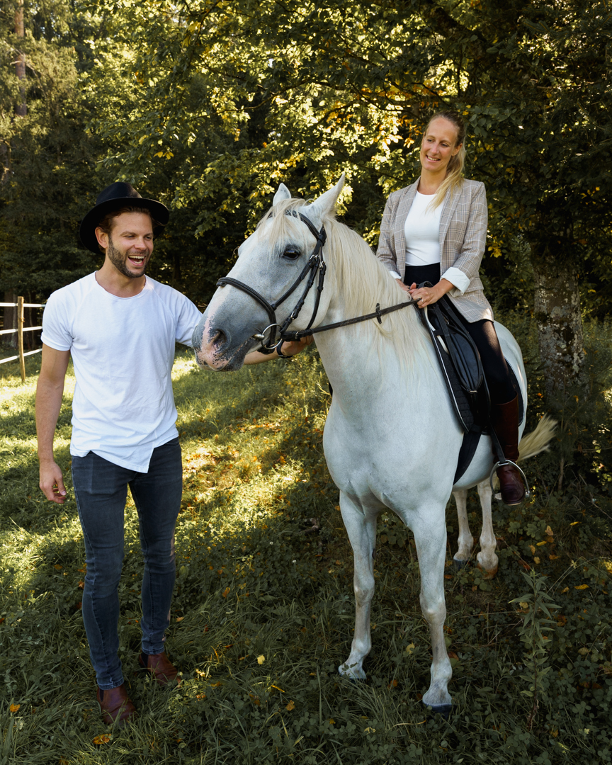 woman in riding outfit sitting on a white Lipizzaner horse, man holding the horse
