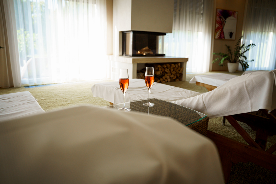 Relaxe beds in the spa area with a fireplace, two glasses of sparkling rose wine standing on a small table