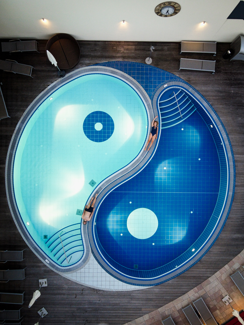 yin and yang shaped pool from above, a man and a woman laying there